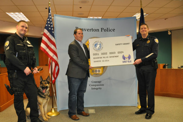 Image Caption – Spirit of Blue presented a $2,500 grant to the Beaverton Police Department for the acquisition of a new K9 working dog, sponsored by the Planet Dog Foundation. The grant was presented by Ryan T. Smith of Spirit of Blue (center) and was received by (left to right) Officer Matt Barrington, K9 Atlas and Chief Geoff Spalding.