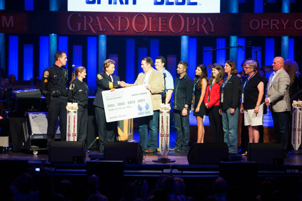 Image Caption - Sgt. Brian Woodward, Officer Rachel Gober and Chief Deb Faulkner of the Franklin Police Department (TN) (left to right) accepted the Spirit of Blue Safety Equipment Grant on the Grand Ole Opry stage, August 19th. The grant was presented by Spirit of Blue representatives Ryan T. Smith, Andrew Heltsley, Craig Morgan, Melissa Norrod, Kara Palm (Krispy Kreme Doughnuts), Sue Post, Diane Harbour and Todd Parola. © 2014 Grand Ole Opry. Photo by: Chris Hollo