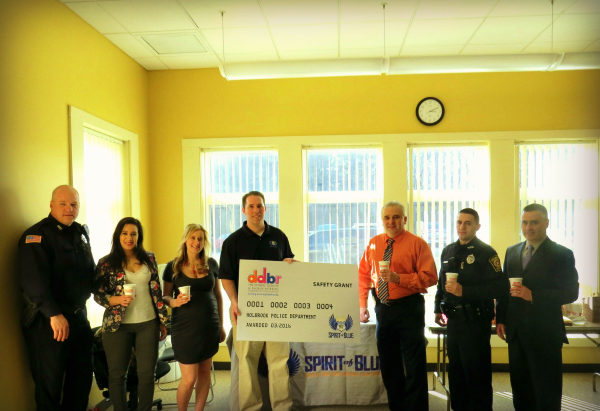Image Caption – Chief William Smith (center right) accepted the Spirit of Blue safety grant on behalf of the officers of the Holbrook Police Department, along with Town Administrator Timothy Gordon (far right). Presenting the grant was Spirit of Blue Executive Director, Ryan T. Smith (center left) and local Dunkin' Donuts franchise owners Monica MacFarlane and Nicole Loredo.