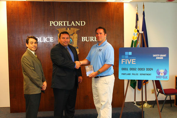 Image Caption - A formal presentation of the Amped Five Safety Equipment Grant was made to members of the Portland Police Bureau Forensic Evidence Division at their Central Precinct. At the presentation were (left to right) Mr. Chris Wormdahl, Police ID Technologies Coordinator; Sgt. Ron Mason, Forensic Evidence Division Supervisor; and Ryan T. Smith, Spirit of Blue Vice-Chairman of Grants and Sponsorships.