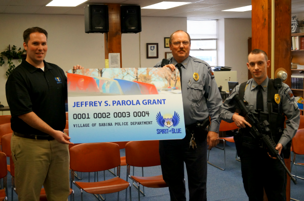 Image Caption - Ryan T. Smith, Vice-Chairman of the Spirit of Blue Foundation, presented the Village of Sabina Police Department with the first annual Jeffrey S. Parola Safety Equipment Grant. Receiving the grant was Chief Keynon Young (center) and Sgt. Adam Day (right) who modeled the rifle and chest rig at a meeting of the Village City Council on February 25, 2014.